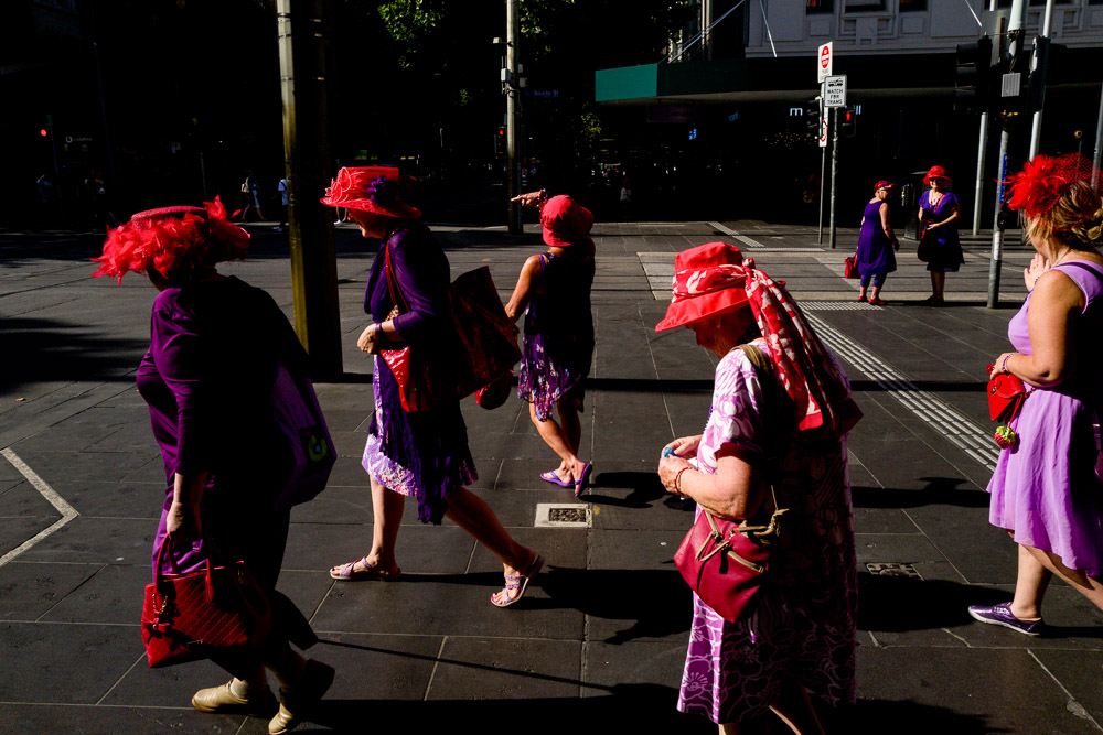 A group of women all wearing red hats and purple clothes walk through a city street in the Melbourne CBD.